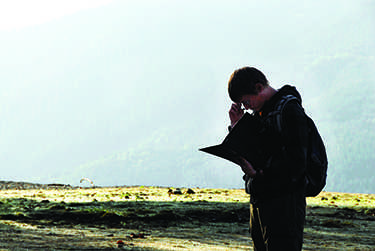 Tyler Annis takes a moment to adjust his glasses while writing notes about Alder Lake while on a field trip taking his class to Mt St Helens and Mount Rainier.
