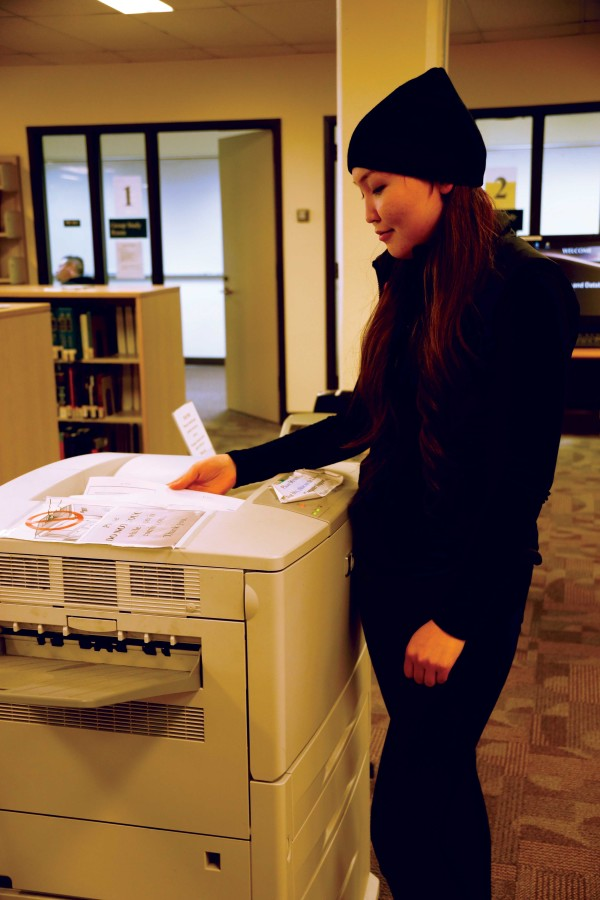EvCC student Bishrel Tamir using the printer in the library to work on her business assignment.