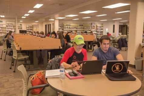 Elma Jensen and Yoshi Cortes, EvCC students working on homework in the library. Students fill the computer and study area of the library.