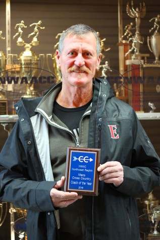 "Frank Dauncey, Cross Country Head Coach, holding up his second award of recognition as ""Regional Coach of the Year."""