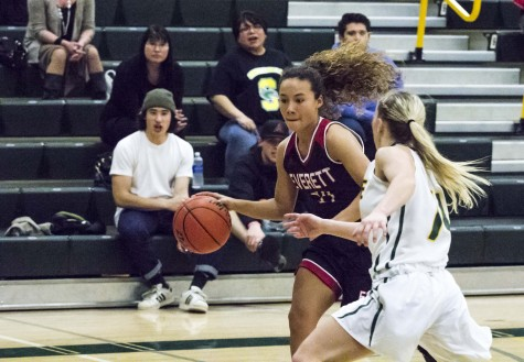 Trojan Guard Riley Zucker driving to the hoop against Shoreline Freshman Dani Hayes looking to keep EvCC on top.