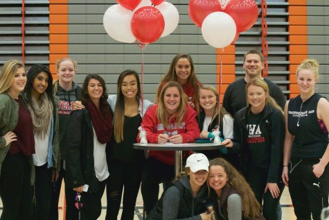 Lauren Allison with all of her friends from the soccer and basketball team, along with her soccer coach Geoff Kittles joining for a group photo, after Allison signed her letter of intent to Saint Martin's University in the Walt Price Fitness Center on Wednesday afternoon.