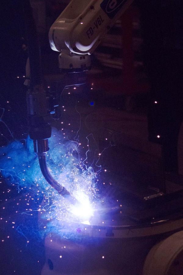 """Air Gas's robotic welding arm in action. Metal name tags engraved with """"Air Gas"""" were submitted to the flame."""