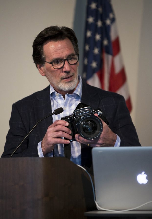 """Paul Matthaeus as he holds a film camera during his presentation in the Jackson Memorial Center on April 13. During his presentation he explained to the audience about the """"8 Rules of Creative Genius"""" and spoke about his participation in creating some of his famous main title sequences."""