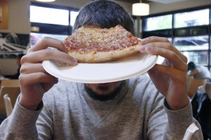 """""""Anonymous"""" in Parks Café during a lunch rush holding up his pizza."""