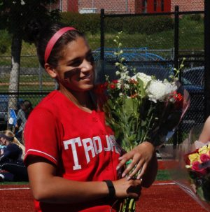 Sophomore Taryn Salter receives a bouquet of flowers from Head Coach Randy Smith on sophomore day at Gaffney Field in front of her family and friends.