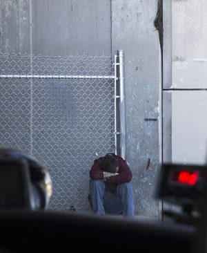 A homeless man sits outside of the Gospel Mission away from others.