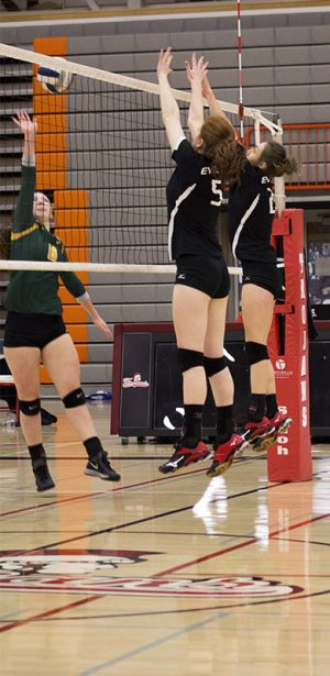 Kendra Lacoste (5) and Tayler Steen (2) elevate above the net in order to block an incoming spike.