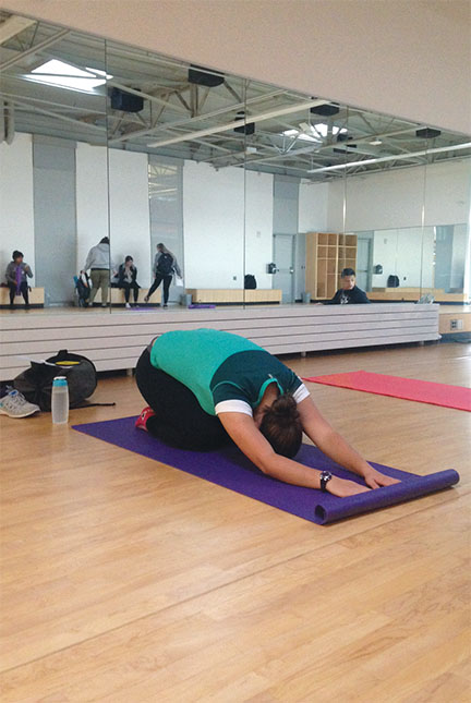 Teagan Fife, a yoga student in Anderson's 8 o'clock morning class, demonstrates the popular Child's Pose.