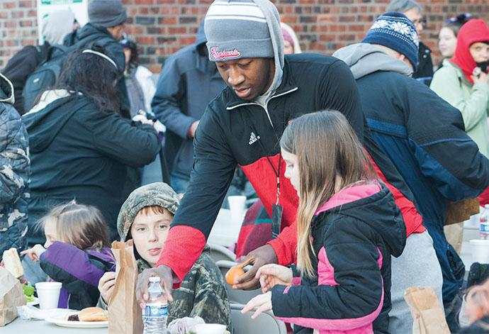Thomas Jones, a sophomore on the EvCC Men's Basketball team, delivers water and fruit to two young attendees at the tailgate.