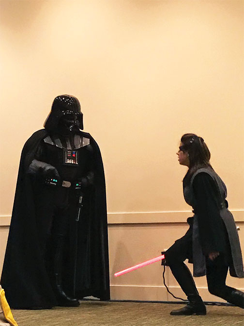 Hannah Lovett, an eLearning Program Specialist, performs for children and their parents as part of the Jet City Saber Guild.