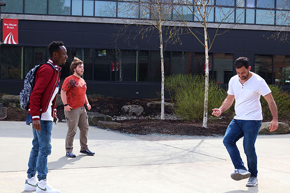 Students were participating in a game of Hacky Sack and more and more people joined in as the time went on. Some students were experts and doing crazy tricks while others were being taught how to play.