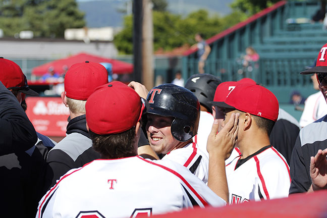 Jaden Yackley and his teammates celebrate in the dugout after scoring a run.