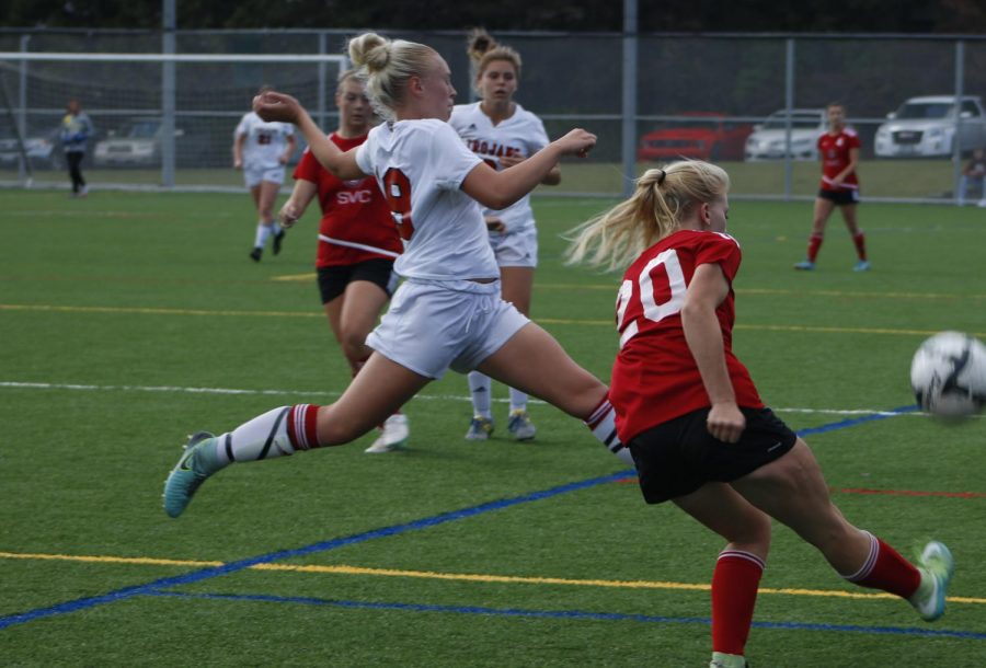 Camryn Cross (left, in white) lunges for the ball as her opponent in red kicks it.