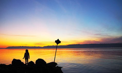 A child on Mukilteo Beach watching as the sun sets over Whidbey Island.