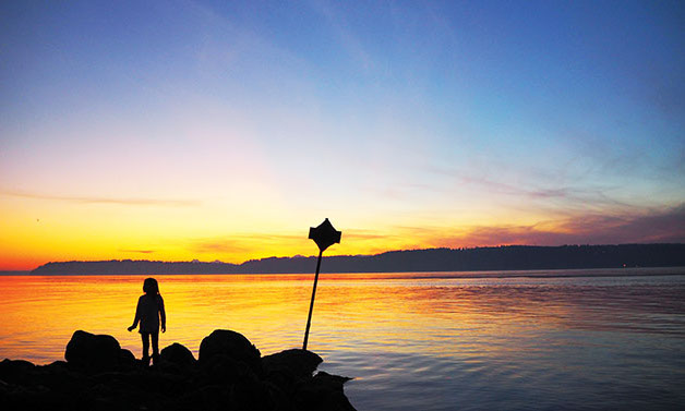 A+child+on+Mukilteo+Beach+watching+as+the+sun+sets+over+Whidbey+Island.