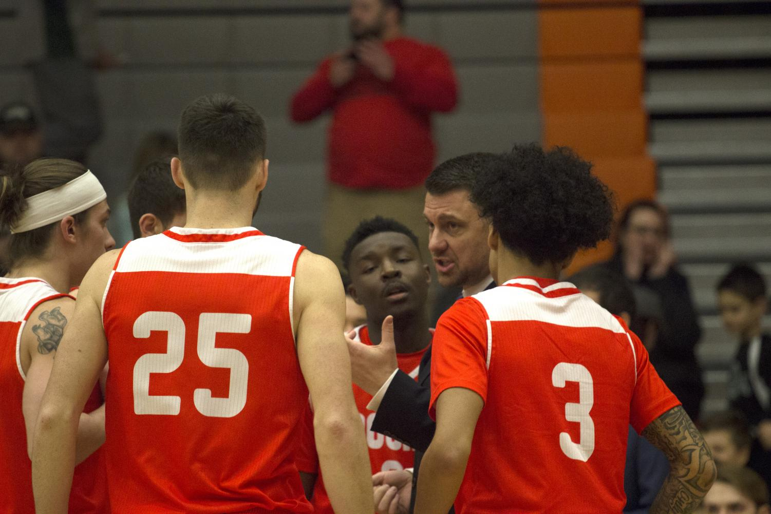 Head Coach Mike Trautman talks to his team in the huddle prior to EvCC's game against Peninsula.