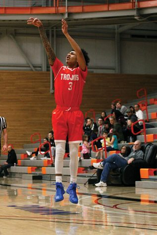 Markieth Brown Jr.  pulls up for a three from the wing in EvCC's game against Peninsula on Feb. 10. Brown led the Trojans to victory with a 27-point outing.