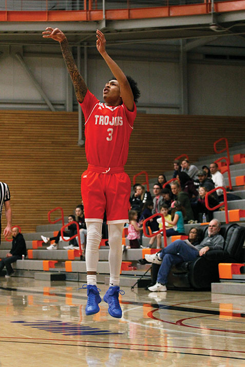 Markieth+Brown+Jr.++pulls+up+for+a+three+from+the+wing+in+EvCC%E2%80%99s+game+against+Peninsula+on+Feb.+10.+Brown+led+the+Trojans+to+victory+with+a+27-point+outing.+