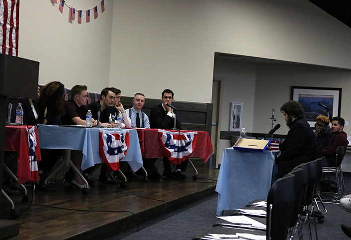 John Yeager, right, moderates the event during the second round of the debate. The Republicans sit at the blue table, and the Libertarians sit at the red table to the right.