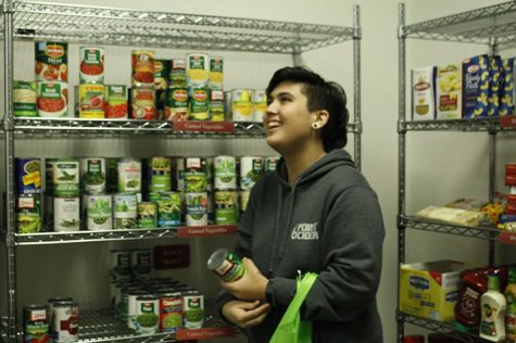 Gabi Lecusay grabs cans from the EvCC food pantry shelves.