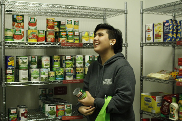 Gabi+Lecusay+grabs+cans+from+the+EvCC+food+pantry+shelves.