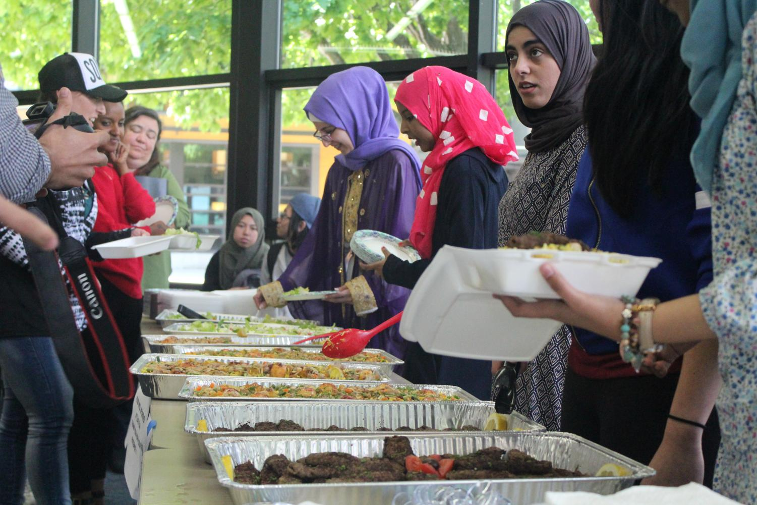Students and event attendees gather around a table to partake in the Ramadan feast.