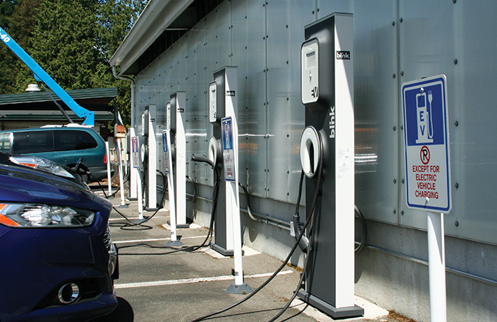 """Charge it! Electric vehicle charging stations, located near the maintenance building, were provided by sustainability grants. Lately, those grants have been harder to come by. Molly Beeman, EvCC's Sustainability and Resource Conservation Manager, says the proposed green fee """"can actually help this college move towards lower emissions goals because the money will be collected from, but managed by and distributed by, students."""" Max Tinsley affirms, """"It's entirely on the student's terms. The benefit of that is we get to decide what our campus does. Every little project impacts us in some way… directly or indirectly."""""""