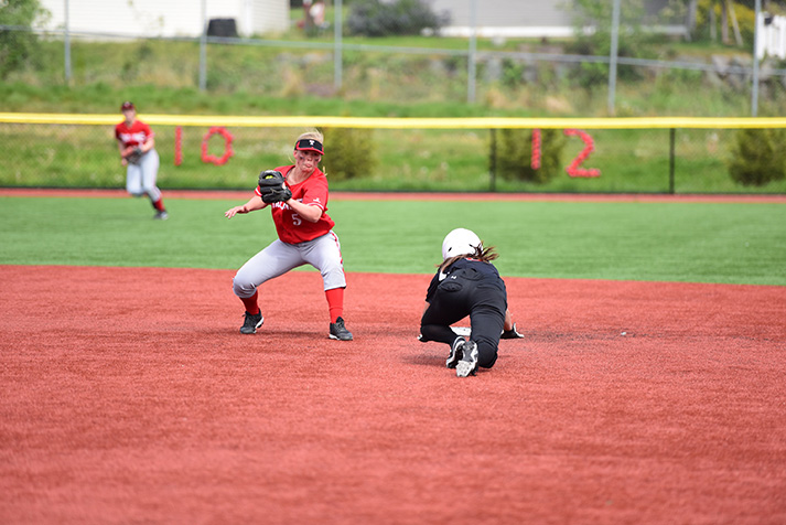 Megan+Dedrick+looks+to+tag+a+runner+sliding+in+to+second+base.