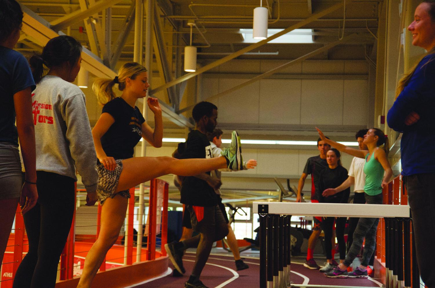 Kicking it during warm up drills with Kaitlin Morgan (left). Coach Tansey Lystad (right foreground) leads cross country practice on Monday Oct. 8 at the Walt Price Student Fitness Center.