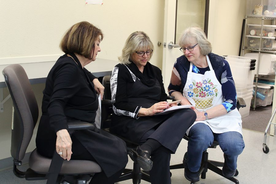 Friends Shirley Sorensen (left), Nancy Purcell (center) and Dianne Engelsen (right) look over the recipes for the dinner. This was the trios first time coming to the Community Kitchen Club.