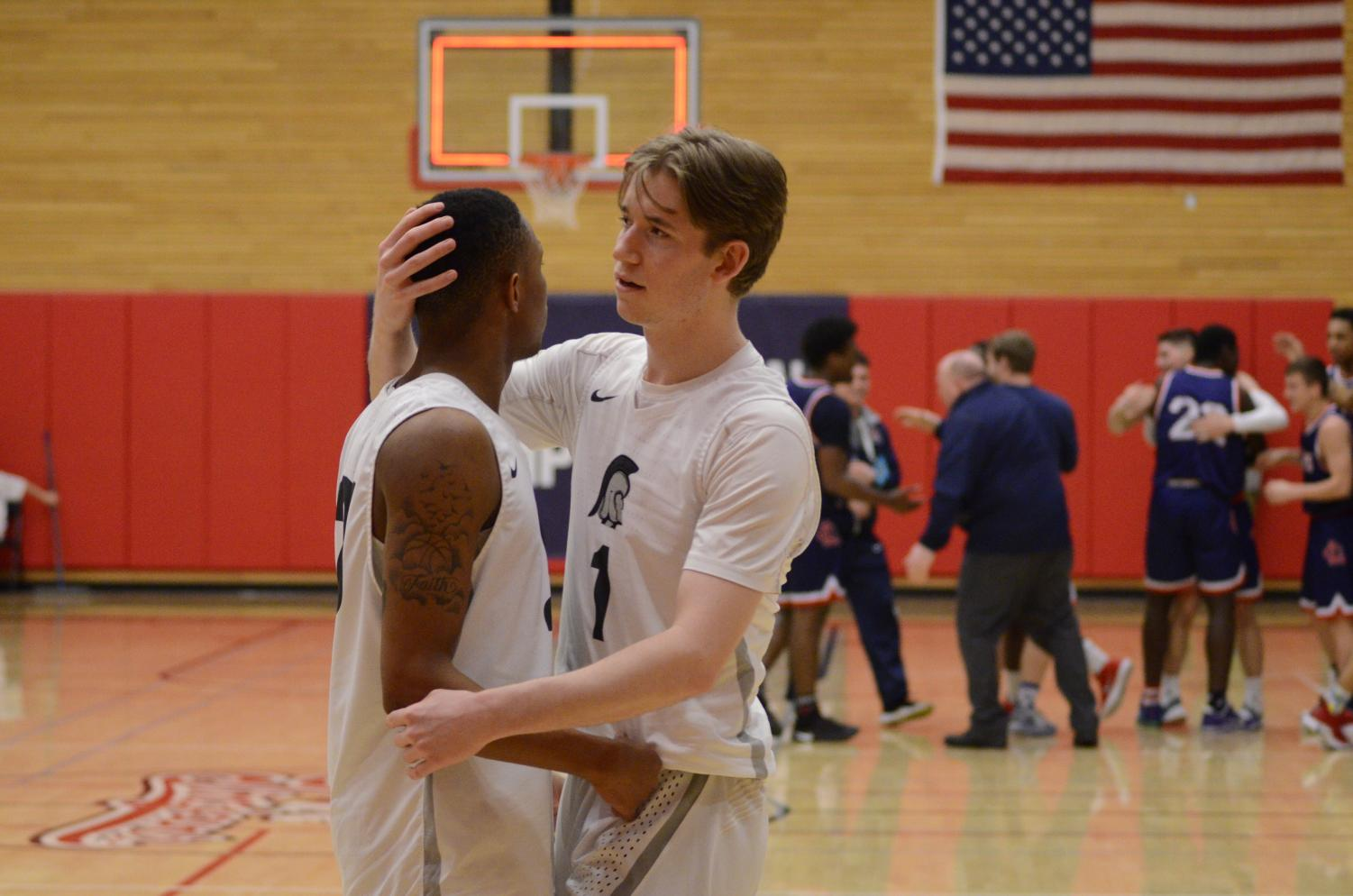 Trojans teammates Tori Odom (left) and Jon Parker (right) comfort one another as the Red Devils celebrate in the distance after the final buzzer in Thursday night's season-ending tournament loss to Lower Columbia College.