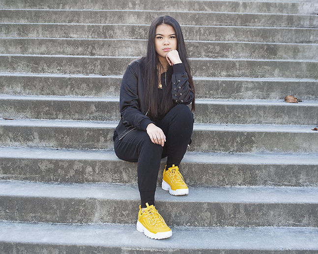 Artist, fashionista and EvCC Running Start student, Pauline Bordon, likes to add a pop of color to a monochromatic look to make her outfit stand out. She is pictured wearing an all-black outfit with a pop of yellow chunky Fila Disruptor II shoes.