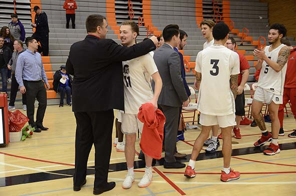 Sophomore guard, Brett Johnson (right) embraces head coach, Mike Trautman (left) after defeating Bellevue College to go undefeated for the first time in program history.