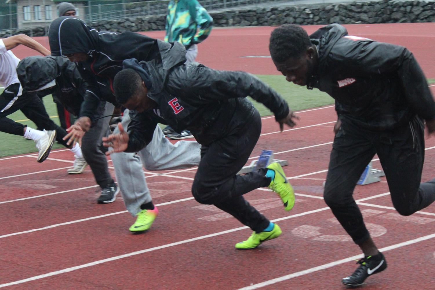 Dimeji Adekanbi (second from right) runs the 100 meter at track practice.