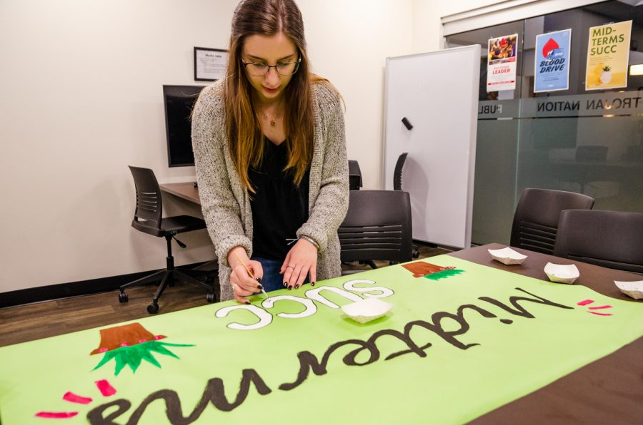 Sofie Havlerson paints posters in preparation for the Midterms Succ event on Monday, May 13.