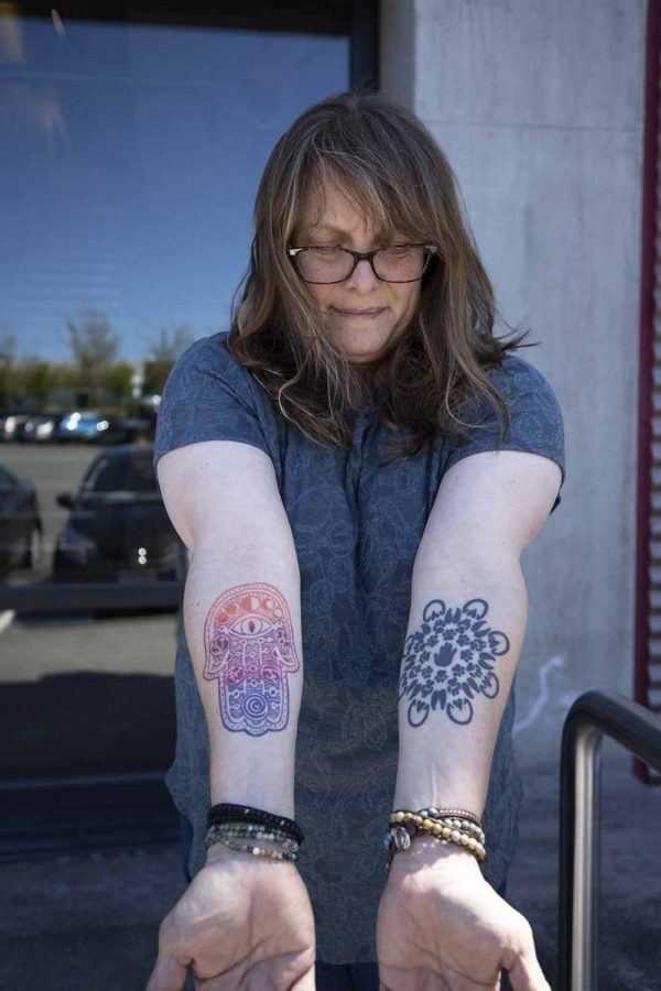 Photography+instructor+Ellen+Felsenthal+recently+got+her+Hamsa+hand+tattoo+at+Tattoo+Garden+in+Everett.+Felsenthal+really+wanted+a+colorful+tattoo+that+would+really+stand+out%2C+so+she+got+all+the+line+work+in+color+opposed+to+filling+in+black+outlines.+Felsenthal+really+personalized+the+inside+designs+on+her+Hamsa+hand+tattoo%2C+every+element+has+a+specific+meaning+to+her.+%E2%80%9CI+had+the+human+eye+replaced+with+a+cat+eye%2C+I+also+added+moons+and+the+symbols+to+represent+the+environment%2C%E2%80%9D+she+says.+Felsenthal+also+personalized+her+other+tattoo%2C+which+is+a+Mandela+made+with+animal+footprints.+