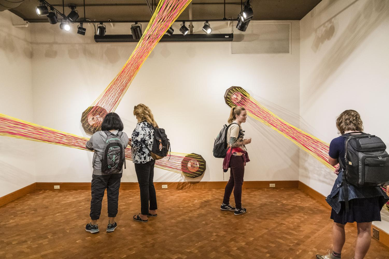 EvCC students observing Henry Jackson-Spieker's art exhibit.