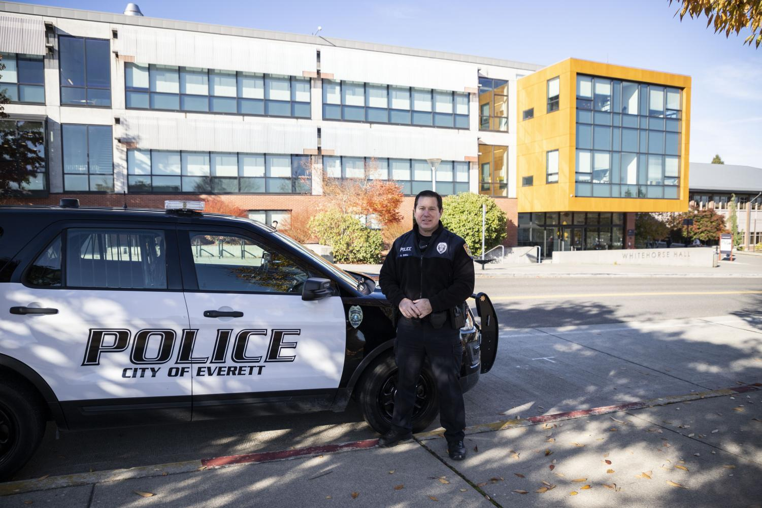 Everett Police Department's Public Information Officer, Aaron Snell stands next to his patrol car and explains the close work between the EvCC's Security Office and the Everett Police Department outside of White Horse Hall on Wednesday, Oct. 30.