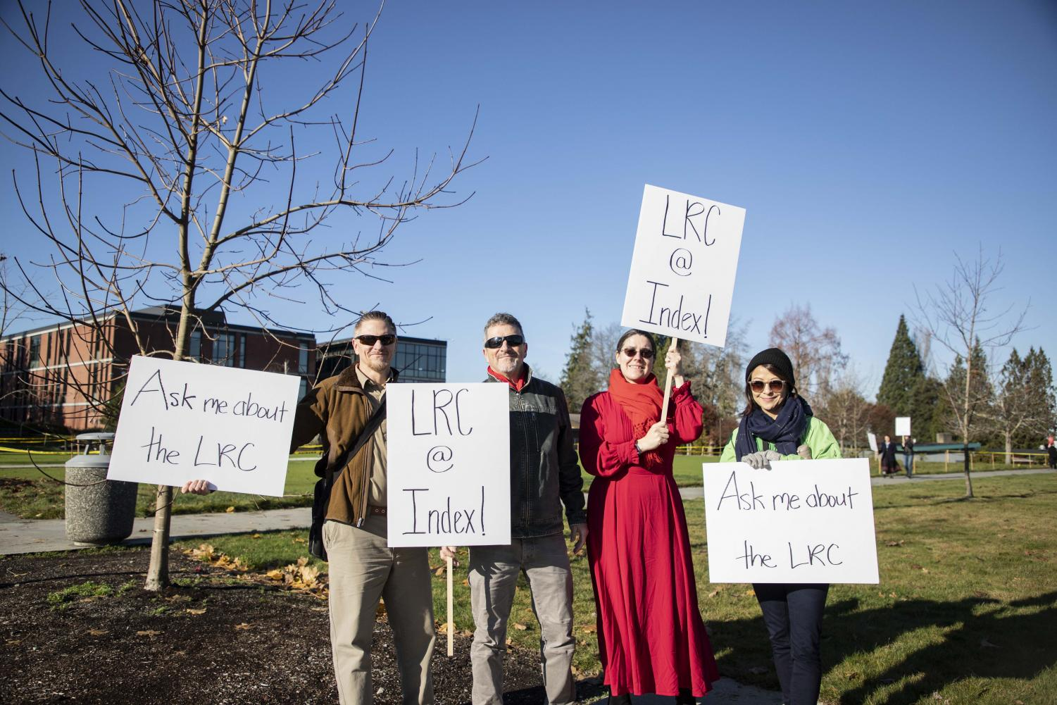 (From left to right) EvCC faculty, Mike VanQuickenborne, Robert Bertoldi, Heather Jean Uhl and Miki Aspree display their picket signs at the LRC protest on Wednesday, Nov. 20 at the Index greenspace.