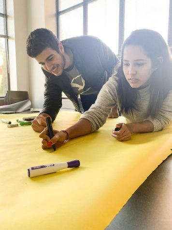 Club members, Vitor Cardozo and Leysky Fernandez, preparing a sign inviting students to join the new Hispanic and Latinx Club.