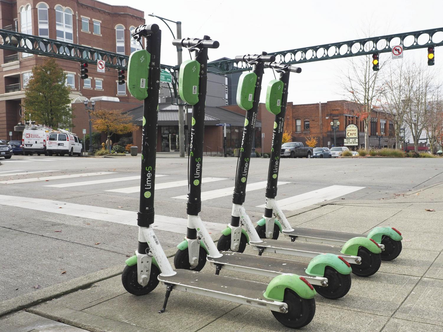 """Lime scooters parked on the corner of Colby and Hewitt in Everett. """"They are heavier than I expected and a little wobbly at first but I really like Lime scooters,"""" said Madison Efaw, an EvCC nursing student."""