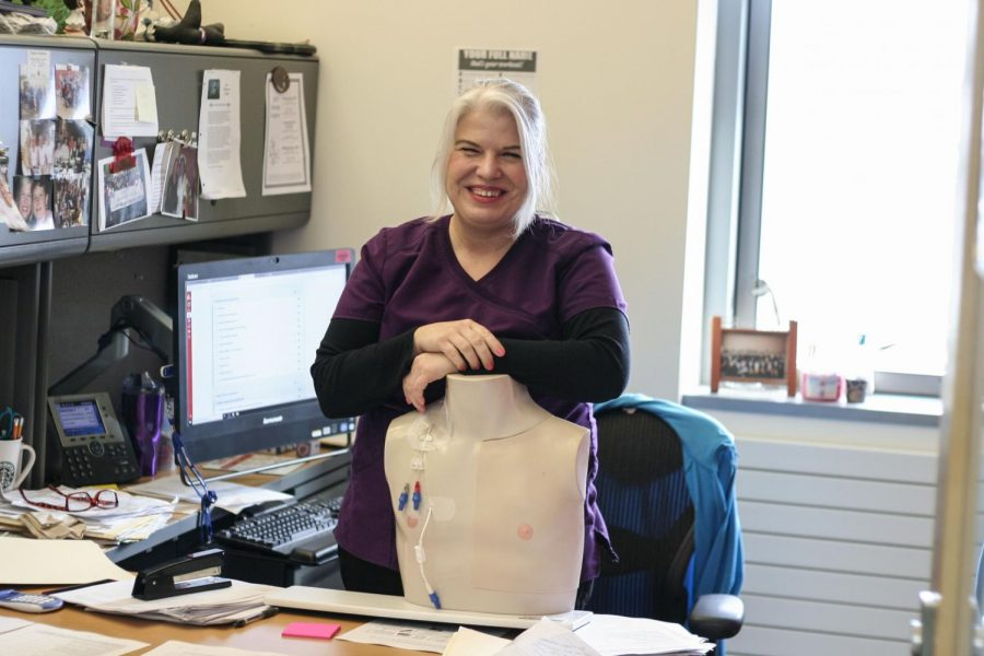 EvCC nursing instructor, Candace Whedon poses for a photo by her desk that is cluttered with piles of paperwork from the snowed-out week.