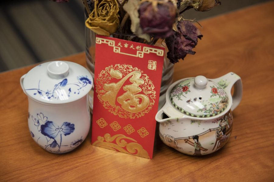 Traditional Chinese New Year red envelope surrounded by dried flowers, a porcelain teacup and teapot.