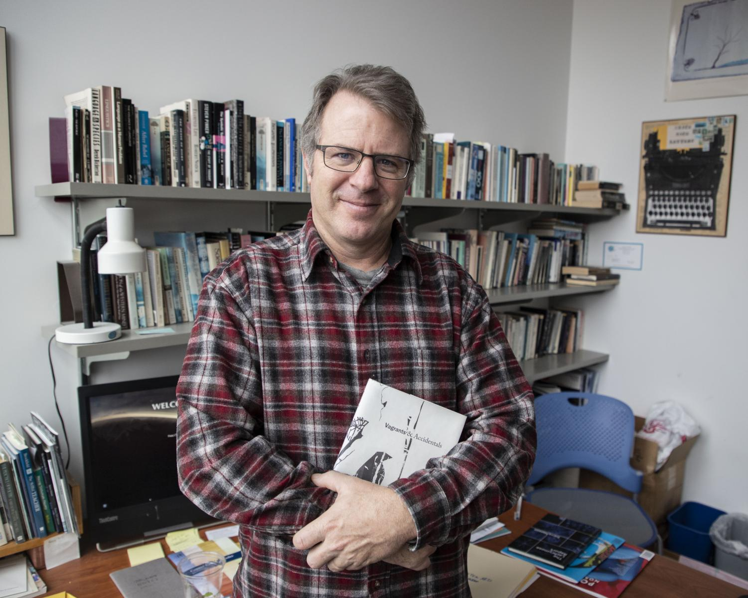EvCC's Written Arts Coordinator, Kevin Craft, holding his poetry book,