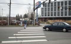 A car closely approaches a pedestrian crossing the street at the North Broadway Ave. and Tower St. intersection. When the LRC is relocated this is one of the crosswalks that students will have to use.