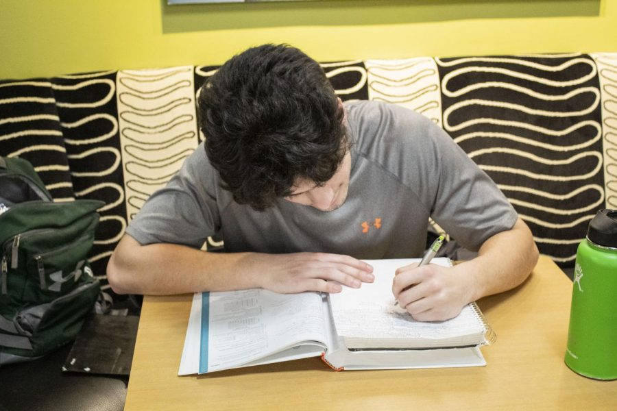 EvCC student, Gabe Birens studying from a textbook inside the Parks Student Union building.