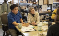 Ceramics instructor, Thom Lee (left), working with student Ann Morgan and others in the ceramics classroom located in White Horse Hall.