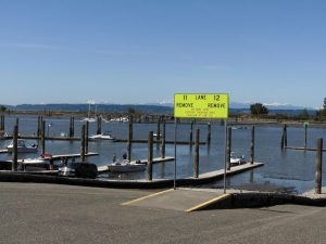 Several boats being launched follow the rule of one per dock and of maintaining a 6-ft distance.