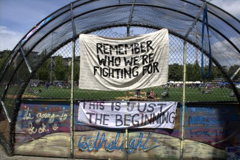 "Banners reading ""Remember Who We Are Fighting For"" and ""This Is Just The Beginning"" are hung at Cal Anderson Park in the area of the Capitol Hill Occupied Protest (CHOP)."